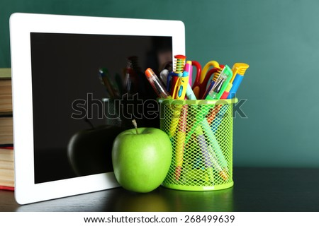 Digital tablet, books, colorful pens and apple on desk in front of blackboard - stock photo
