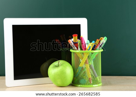 Digital tablet,  colorful pens and apple on desk in front of blackboard - stock photo
