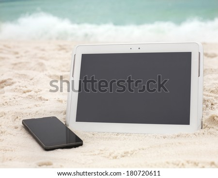 Digital tablet computer and smartphone on ocean beach - stock photo