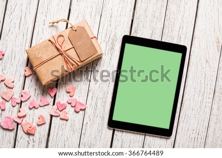 Digital tablet computer and vintage gift box with gift tag on white wooden background. Clipping path included. - stock photo