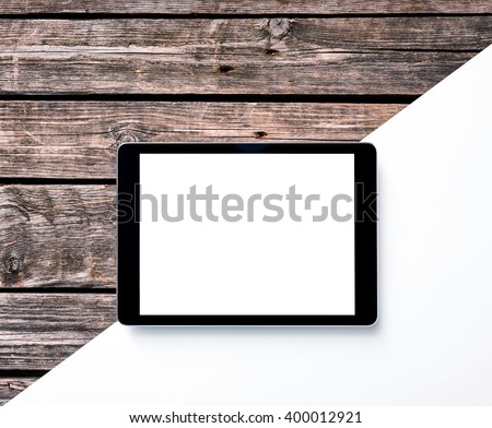 Digital tablet computer on wooden desk. Clipping path for display included.