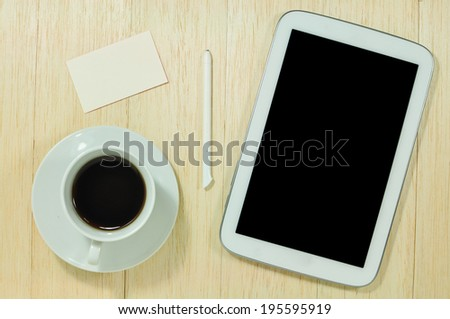 Digital tablet computer with  business card and cup of coffee on wooden desk.