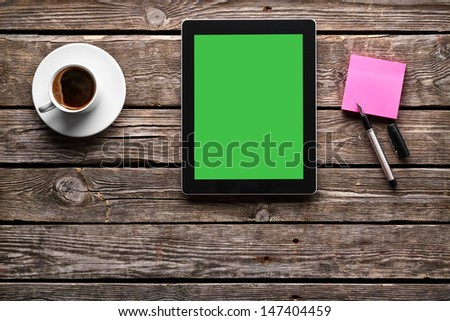 Digital tablet computer with cup of coffee on old wooden desk. Top view. - stock photo