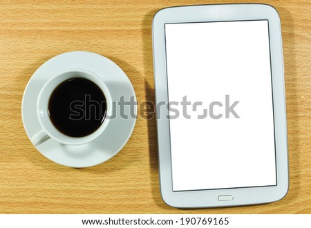 Digital tablet computer with cup of coffee on wooden desk.