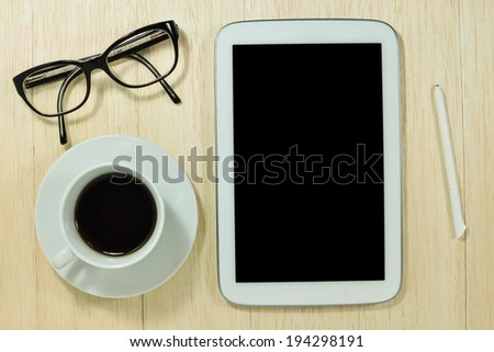 Digital tablet computer with glasses and cup of coffee on wooden desk.