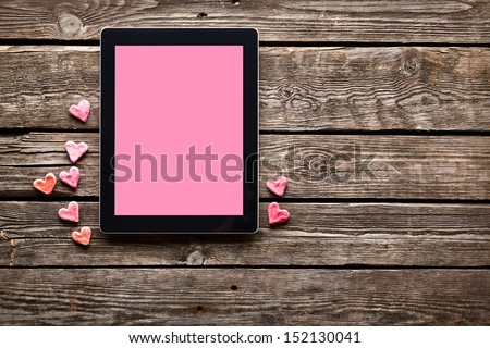 Digital tablet computer with isolated screen and with small red hearts on old wooden desk. - stock photo