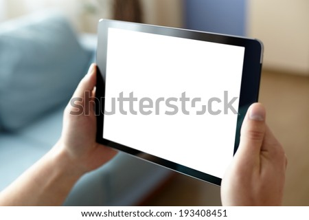 Digital tablet computer with isolated screen in male hands over home or office background - stock photo