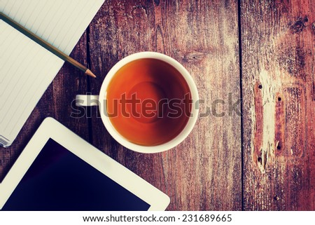 Digital tablet computer with note paper and cup of tea on old wooden desk. Simple workspace or tea break / selective focus - stock photo