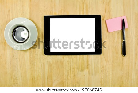 Digital tablet computer with sticky note paper and cup of coffee on wooden desk. - stock photo