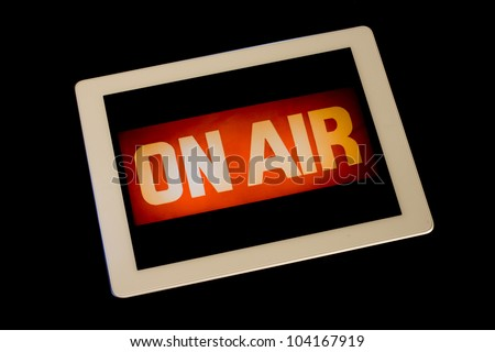 Digital Tablet displaying traditional television broadcast on-air sign symbolizing internet television, webstream, digital television, webcast or web tv.  Blue tech lighting around edges on black.