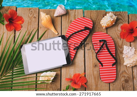 Digital tablet, flip flops and hibiscus flowers on wooden background. Summer holiday vacation concept. View from above - stock photo