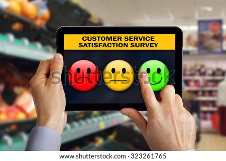 Digital tablet in shop with customer rating a service satisfaction questionnaire survey choosing a happy smiley emoticon - stock photo