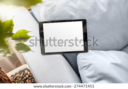 Digital tablet on a blue leather sofa. Clipping path included. - stock photo