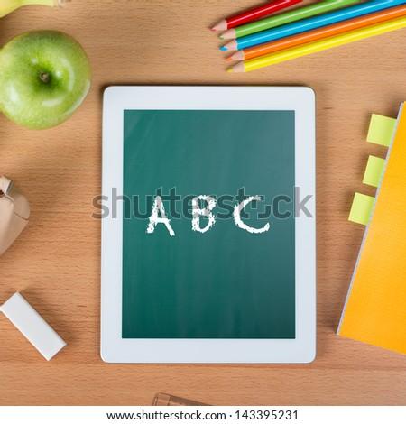 Digital tablet on a school desk with ABC written between a paper notebook, pencils, an eraser, and an apple - stock photo