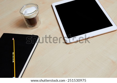 Digital tablet on a wooden desk with coffee and organiser
