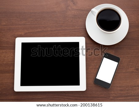 Digital tablet on wooden tablets with mobile and coffee - stock photo
