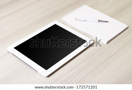 digital tablet on wooden tablets with notepad and pen - stock photo