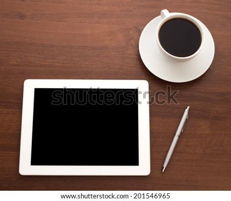 Digital tablet on wooden tablets with pen and coffee
