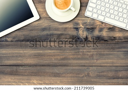 digital tablet pc, keyboard and cup of coffee on wooden table  - stock photo