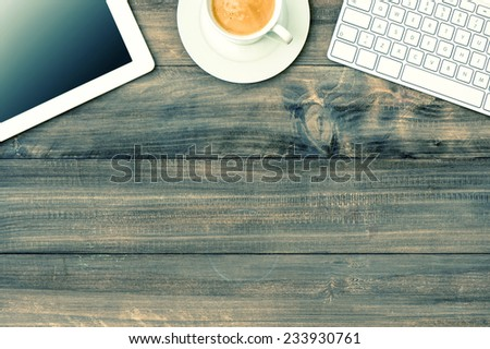 digital tablet pc, keyboard and cup of coffee on wooden table. mock up. vintage style toned picture - stock photo