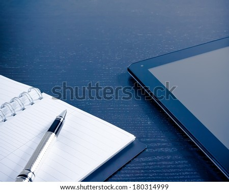 digital tablet pc near notes in the office on wood black table, concept of new technology - stock photo