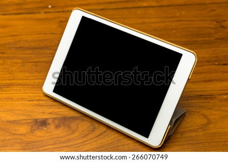 Digital tablet PC on wood office table. - stock photo