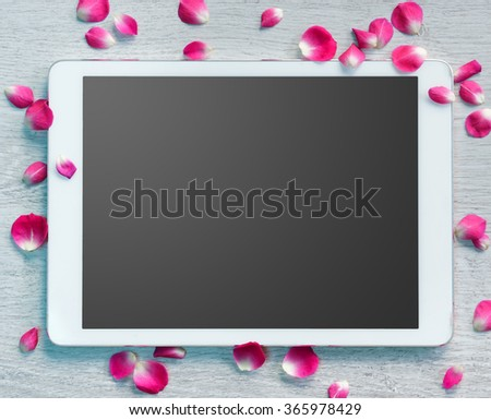 Digital tablet screen with small petals on white wooden background.Valentines Day background and Copy space for your text