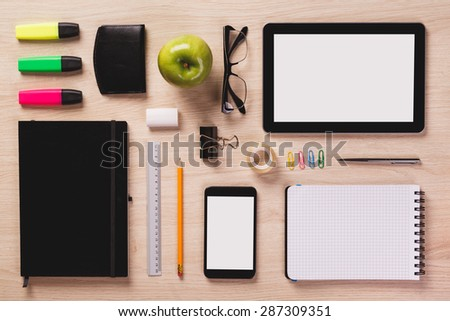Digital tablet, smartphone, notepad, pen, pencil, rubber, green apple, calendar, highlighters and other office equipment arranged in perfect order on bright wooden office desk. - stock photo