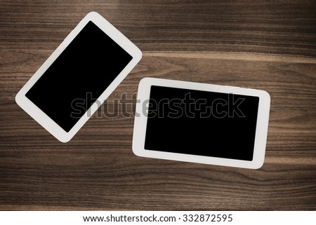 Digital tablet, white smartphone phone on old wooden desk table. Simple modern mobile workspace working business or web surfing. Dark color on screen. Lot of free spare copyspace for your content. - stock photo