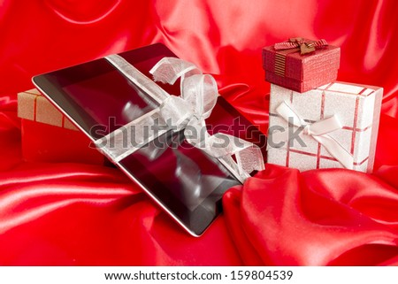 Digital tablet with christmas presents on red background