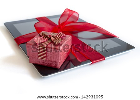 Digital tablet with red ribbon gift isolated on white. - stock photo