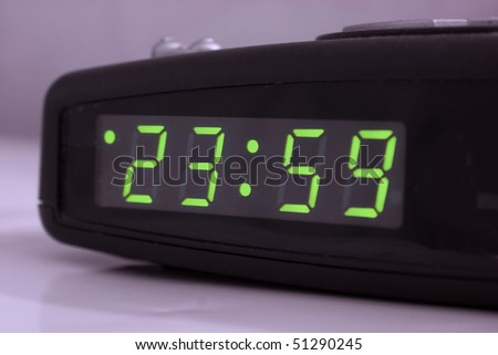 Digital tabletop clock showing one minute to midnight 23.59 - stock photo