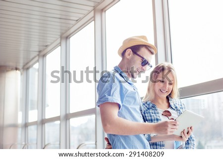 Digital technology and traveling. Young loving couple in casual wear using tablet computer while standing in the airport terminal waiting for boarding. - stock photo