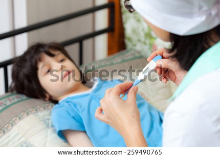 digital thermometer in the hands of a doctor. Temperature measurement in the child. home medicine - stock photo
