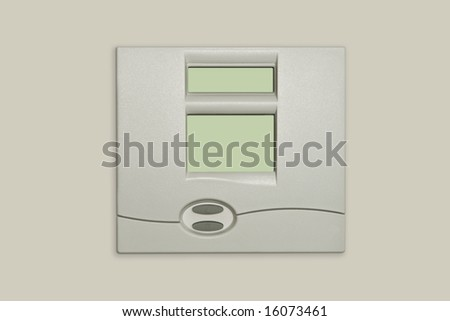 digital thermostat isolated against beige wall - stock photo