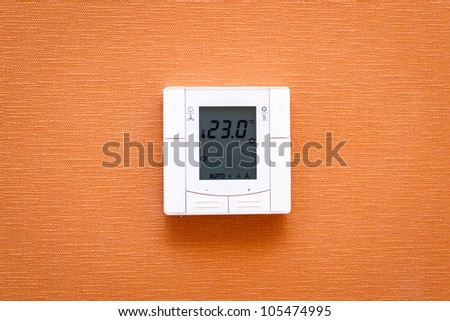 Digital thermostat on wall - stock photo