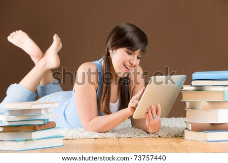 Digital touch screen computer - woman teenager study at home - stock photo