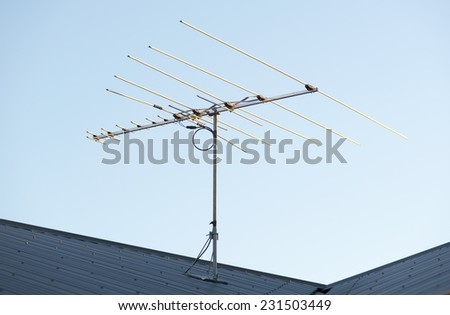 Digital TV aerial or antenna on top of a house - stock photo