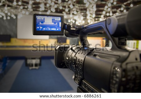 Digital video camera shoots meeting - 3CCD Camcorder recording in TV studio - stock photo