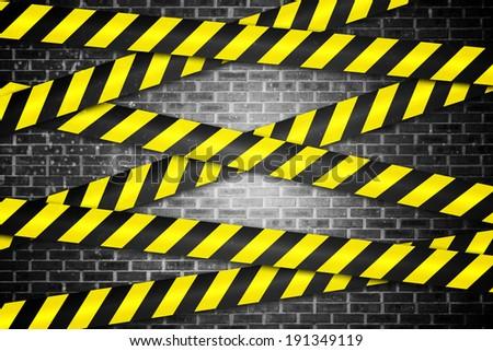 Digitally generated cordon tape over grey wall - stock photo