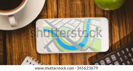 Digitally generated image of map against smartphone on desk - stock photo