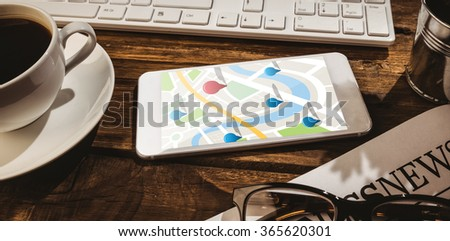Digitally generated image of navigation pointers against smartphone on desk - stock photo