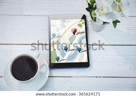 Digitally generated image of navigation pointers against tablet on desk - stock photo