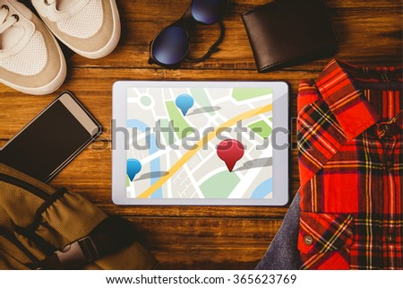 Digitally generated image of navigation pointers against tablet shirt jean shoes smartphone wallet and bag - stock photo