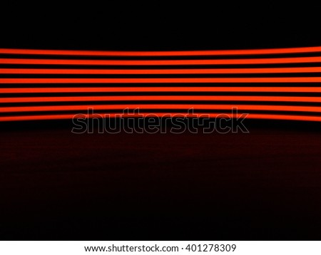 Digitally generated image of red light line over black background on black wooden table - stock photo