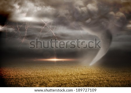 Digitally generated stormy sky with tornado over field