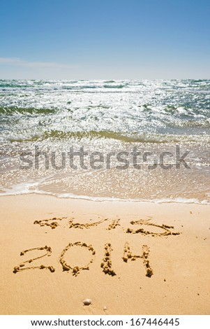 digits  2013 and 2014 on the sand seashore - concept of new year and passing of time - stock photo