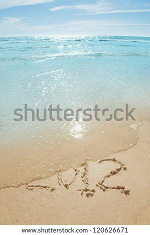 digits 2012 on the sand seashore - concept of new year and passing of time - stock photo