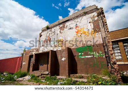 Dilapidated brown old building with rubbish in front of it, and blue skies and white clouds above - stock photo