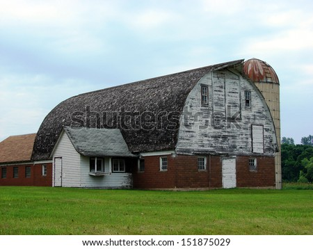 dilapidated old building large barn with silo - stock photo